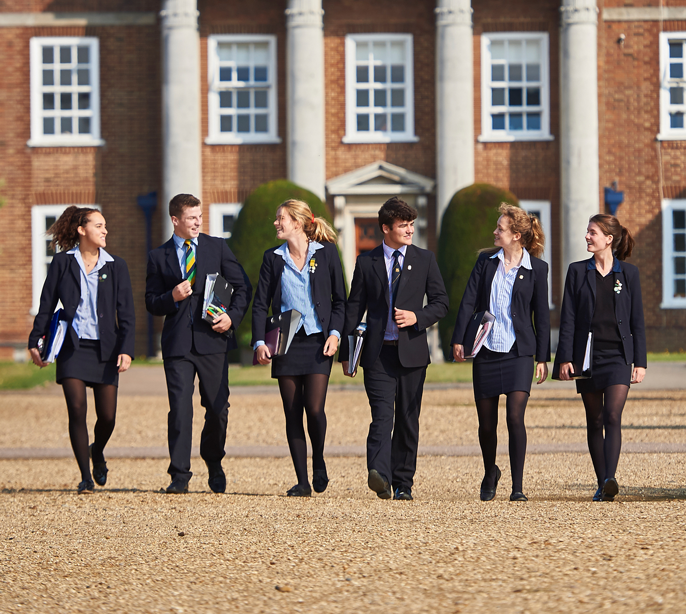 Sixth Form pupils walking together in front of the Royal Hospital School building